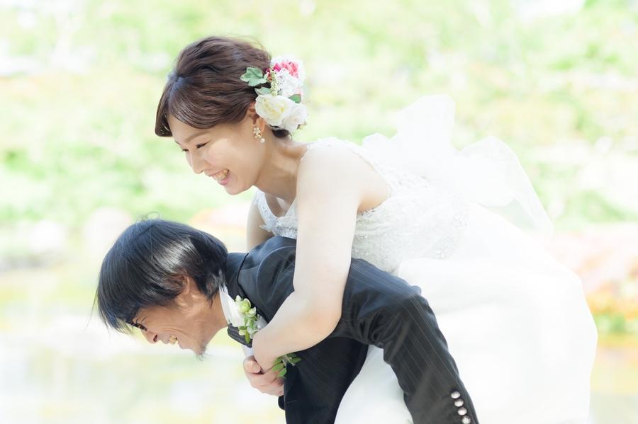 撮影に疲れたお嫁さんをおんぶしてあげる優しい新郎さん